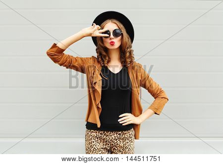 Fashion Pretty Woman Wearing A Black Hat, Sunglasses And Jacket Having Fun Over Urban Grey Backgroun