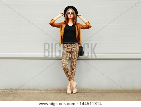 Fashion Pretty Young Woman Wearing A Retro Elegant Hat, Sunglasses, Brown Jacket And Black Handbag P