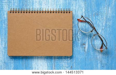 Brown notebook with glasses on blue wooden floor.