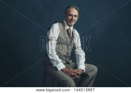 Confident Retro 1920S Fashion Man Sitting On Wooden Chair In Empty Room.