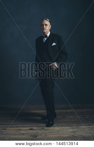 Middle Aged Retro 1920S Businessman In Black Suit With Bow Tie.