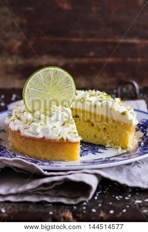 Pound cake with lemon, lime and freshly shredded coconut with cream cheese frosting, selective focus