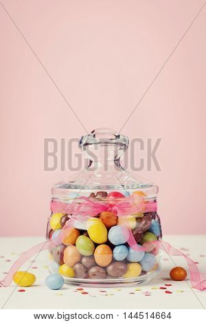 Colorful candy jar decorated with bow ribbon against pink background for Birthday or Easter holiday.