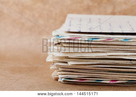 Stack of old envelopes and letters on kraft paper.