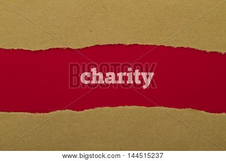 Charity word written under torn paper .