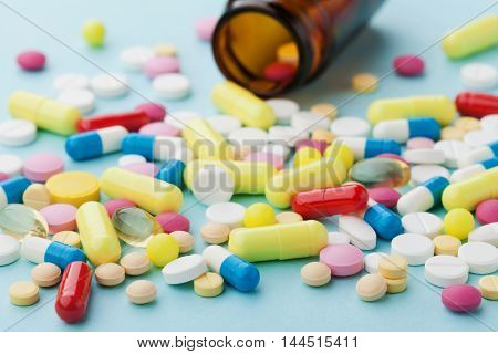 Colorful drug pills on blue background. Pharmaceutical and medical concept.