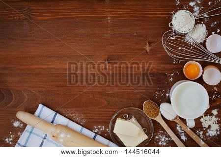 Ingredients for baking dough such as flour, eggs, milk, butter, sugar, whisk and rolling pin on wooden rustic background. Empty space for recipe. Top view. Flat lay.