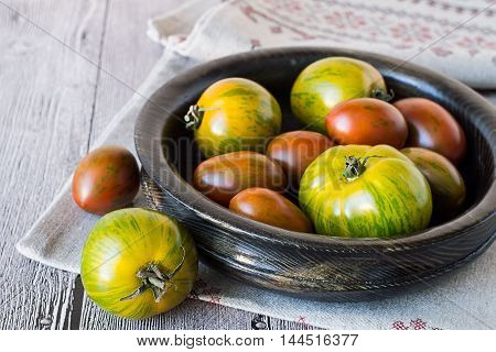 Freshly picked tomatoes in a wooden bowl on a napkin on the old wooden table.