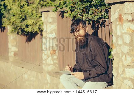 Bearded Man Outdoor With Pencil And Note
