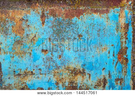 Multicolored background: rusty metal surface with blue paint flaking and cracking texture