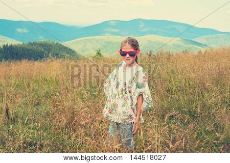 Little girl in hippie style posing on a mountain meadow. Bright red sunglasses and colorful blouse. Vintage. Toned image
