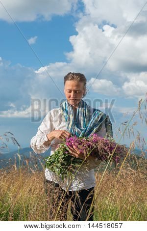 Young woman looks at a bouquet of wild flowers which holds in his hands. Summer day on a mountain meadow. Ukrainian Carpathian mountains