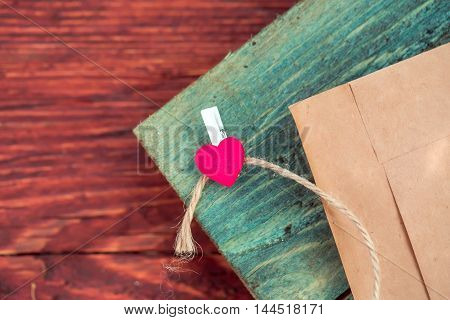 Red heart clothespin on rope and blank brown paper envelope on grey wooden board on timber background