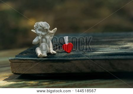 Beautiful cupid angel white porcelain figurine and red heart clothespin on wooden board on natural background