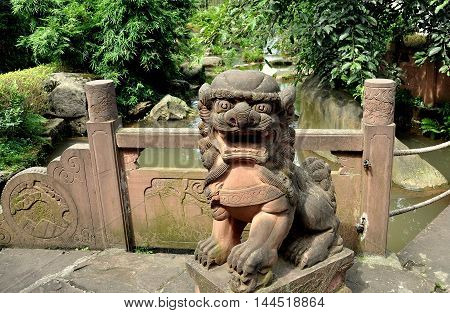 Ping Le Ancient Town China - September 29 2010: A pink sandstone Fu Dog statue stands on a small bridge over a stream with lush plantings