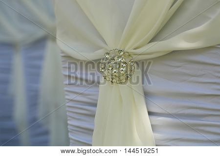Sparkling brooch on beautiful creamy ribbon knot of white chair wedding decoration romantic background