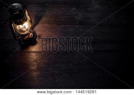 Old-fashioned kerosene lamp on the dark table in twilight. Soft focus