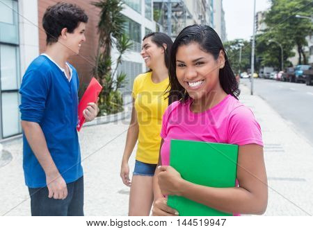 Happy latin female student in pink shirt with other students