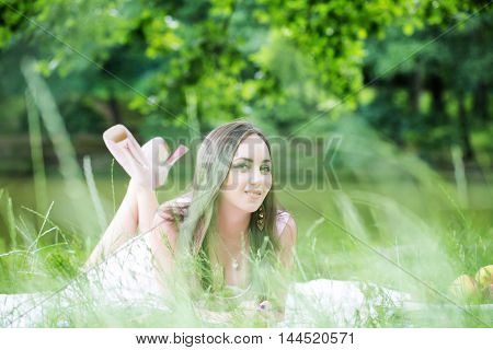 young sexy woman with long brunette hair and pretty smiling happy face laying on plaid on green grass outdoor on natural background