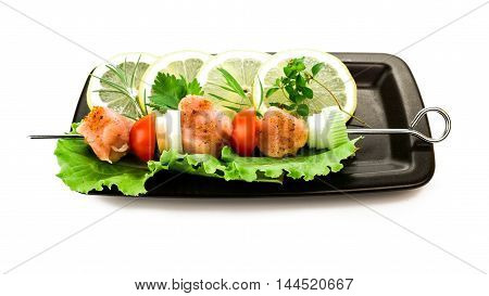 Piece of raw pork and vegetables on grill stick on plate over white background