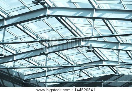 Glass roof in building Under the roof. Glass and metal constructions of modern office building with outside blue sky. Transparent glass panel with a metal frame.