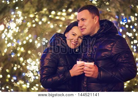 Happy couple drinking hot beverages at winter holidays