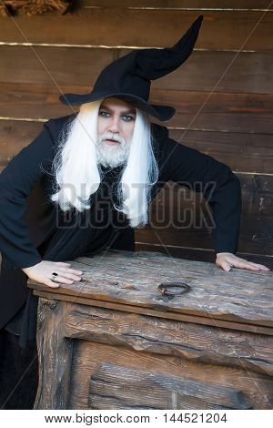 Old Wizard Near Wooden Chest Or Trunk Box