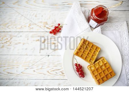 Waffles with red currant jam and berries on a white plate on the wooden background