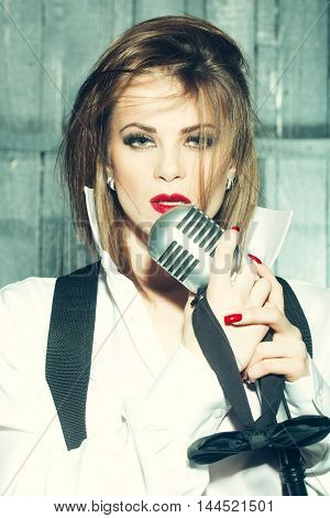 young pretty woman with sexy red lips singing into silver studio microphone in retro braces and shirt holding bow closeup