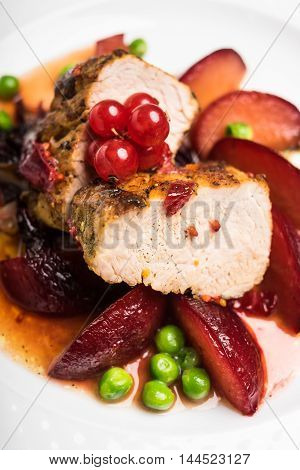 Roasted pork fillet with glazed apples, peas and red currant berry on a plate, selective focus
