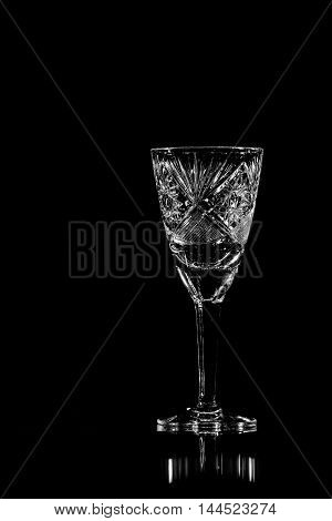 Wineglass of crystal over black reflective background