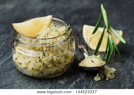 Body scrub of sea salt with lemon, rosemary and olive oil in glass jar on stone table. Homemade cosmetic for Spa care.