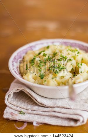 Portion of mashed potatoes with roasted garlic cloves, black pepper and fresh chopped parsley in a bowl with a spoon