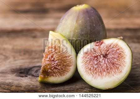 sliced of a fig isolated on wooden background