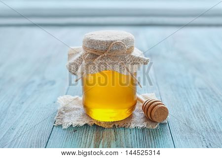 Natural honey in a pot or jar with twine, tied in a bow and honey dipper on a blue wooden background.