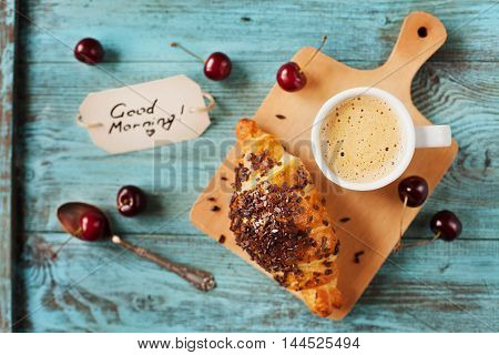 Tasty breakfast with fresh croissant, coffee, cherries and notes good morning on a wooden table. Selective focus on coffee.