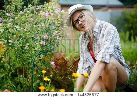smiling girl in glasses and hat sitting next flowers in garden