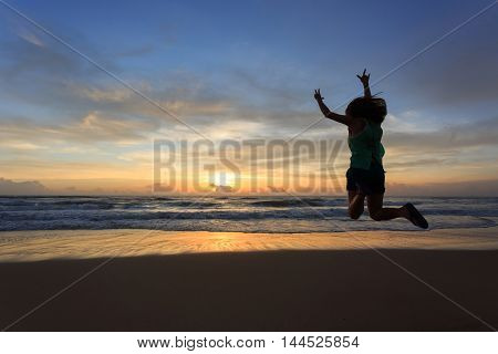 woman traveller happy jumping on the beach with sunrise image of lifestyle freedom life concept