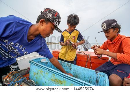 Labuan,Malaysia-Aug 28,2016:Unidentified kids of traditional fisherman prepare baits to fish at Kiansam beach on 28th Aug 2016 at Labuan Pearl Of Borneo,Malaysia.