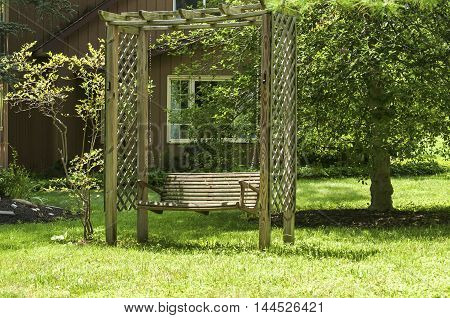 Brown wooden swing in courtyard of country house