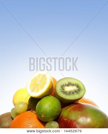 Set of different bright tasty fruits over blue background