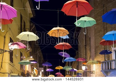 street in Ferrara with colorful umbrellas hanging in the air