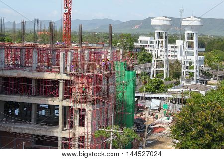 Construction and renovation of tall buildings building under construction in scaffolding in Thailand.