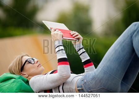 young girl with glasses keeps Tablet lying.Blurred background