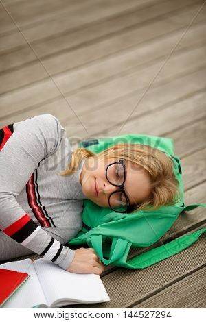 student fell asleep reading lectures on wooden floor