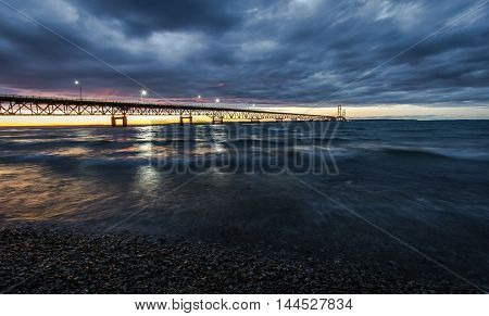 Dramatic Sky Over The Mackinac Bridge. Clouds and sunset sky over the Mackinac Bridge. Located in Michigan, it is the longest suspension bridge in the Western Hemisphere and connects the Upper and Lower Peninsula.