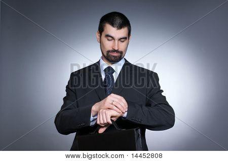 Businessman looking on his watch over dark grey background