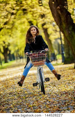 Young and beautiful girl on bike in autumn park.