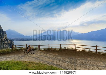 Mountain biking on Sentiero della Ponale, Riva del Garda, Italy. Amazing view of Lake Garda in background.