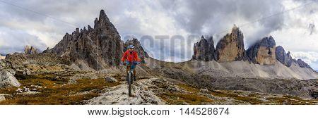Mountain biking in the Dolomites. Amazing panorama of Tre Cime di Lavaredo in background.